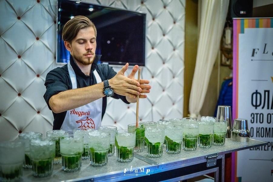 Бармен Андрей сосредоточен на создании коктейлей.